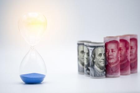 Banknot dolara amerykańskiego i juana z zegarem piaskowym na wojnę handlową między Stanami Zjednoczonymi a Chinami, którą oba kraje walczą, zwiększając barierę podatkową i czas na spotkanie. Rząd i biznes.