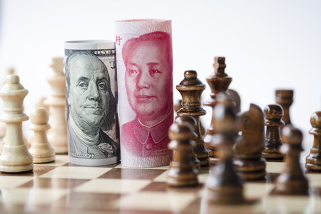US dollar and Yuan banknote with chess for tariff trade war between United States and China which both countries battle by increase tax barrier of import and export product. Government and business. Stock Photo