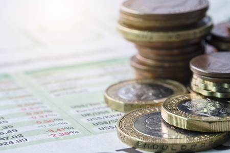 Closeup of stacking of pound sterling coins on exchange rate of newspaper.-Image.