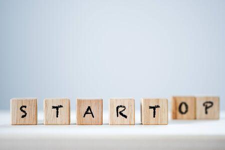 Iniciar y detener la palabra clave en madera cúbica. Esta es una redacción conceptual. Foto de archivo