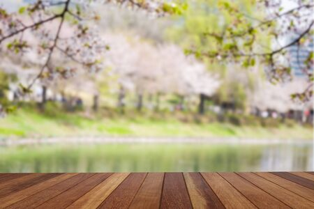 Wooden table for array goods and product of advertisement on blurred beautiful natural green park landscape.