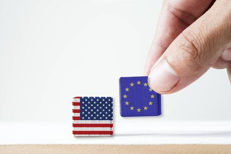 Hand putting print screen EU flag and USA flag wooden cubic on white background.It is symbol of United States of America increase tariff tax barrier for import product from EU countries.-Image.