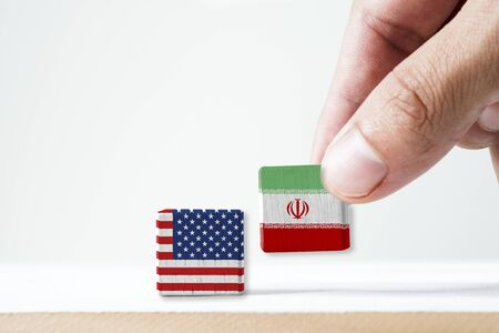 Hand putting print screen Iran flag and USA flag wooden cubic on white background.It is symbol of United state of America and Iran have conflict in nuclear weapons and Strait of Hormuz.-Image.