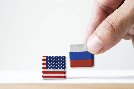 Hand putting print screen Russia flag and USA flag wooden cubic on white background.United state of America  is leader of democracy and Russia is communist after world war two and Cold War.-Image.