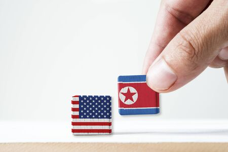 Hand putting print screen North Korea flag and USA flag wooden cubic on white background.It is symbol of conflict for both countries in nuclear weapon military and economic sanction.-Image.