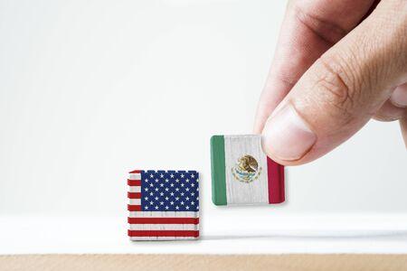 Mano poniendo la pantalla de impresión de la bandera de México y la bandera de Estados Unidos de madera cúbica sobre fondo blanco. Es símbolo de conflicto para ambos países en inmigrante mexicano.-Imagen.