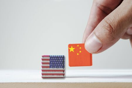Hand putting print screen China flag and USA flag wooden cubic on white background.It is symbol of tariff trade war tax barrier between United States of America and China.-Image.