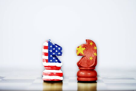 USA flag and China flag print screen on horse chess with white background.It is symbol of tariff trade war tax barrier between United States of America and China.-Image. 스톡 콘텐츠