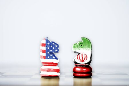 USA flag and Iran flag print screen on horse chess with white background.It is symbol of United state of America and Iran have conflict in nuclear weapons and Strait of Hormuz.