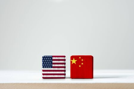 USA flag and China flag print screen on wooden cubic with white background.It is symbol of tariff trade war tax barrier between United States of America and China.-Image.