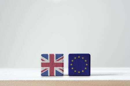 EU flag and British flag print screen on wooden cubic with white background. It is symbol of British need to exit or call BREXIT from European Union members zone. -Image.