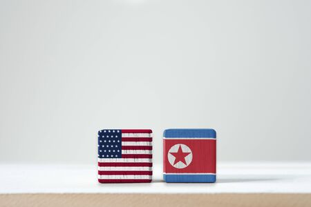 USA flag and North Korea flag print screen on wooden cubic with white background. It is conflict for both countries in nuclear weapon military and economic sanction.-Image.