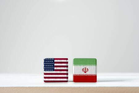 USA flag and Iran flag print screen on wooden cubic with white background.It is symbol of United state of America and Iran have conflict in nuclear weapons and Strait of Hormuz.