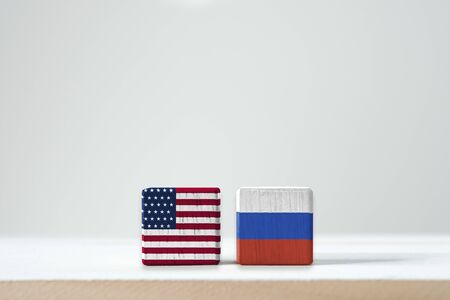 USA flag and Russia flag print screen on wooden cubic with white background.United state of America  is leader of democracy and Russia is communist after world war two and Cold War.-Image. Zdjęcie Seryjne