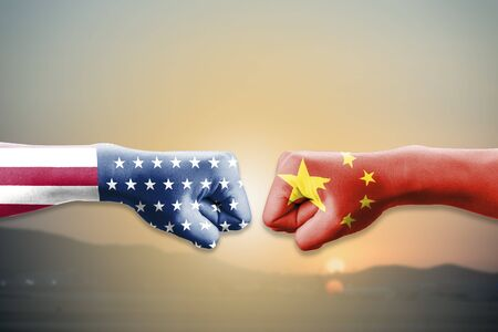 USA flag and China flag print screen on two  fists  for battle on sunrise and landscape. United States of America versus China trade war disputes concept. - Image 스톡 콘텐츠