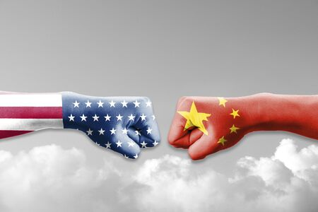 USA flag and China flag print screen on two  fists  for battle on cloudscape. United States of America versus China trade war disputes concept. - Image