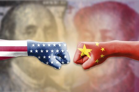 USA flag and China flag print screen on two  fists  for battle on dollar and yuan banknote. United States of America versus China trade war disputes concept. - Image