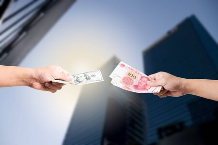 One hand hold dollar banknote and another hand hold Yuan banknote on skyscraper for exchange and trade war concept. -Isolated image.