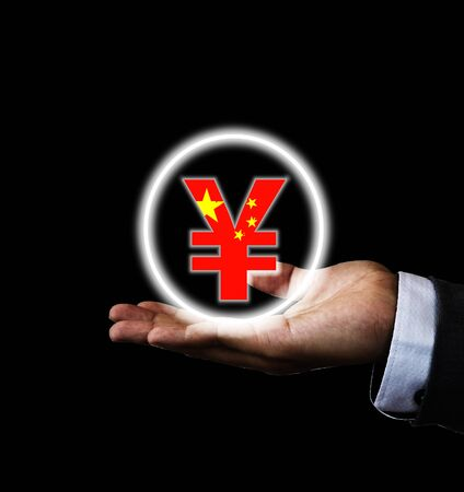 China Yuan sign on hand of businessman with black background. Yuan is main and popular currency of exchange in the world. Investment and saving concept.