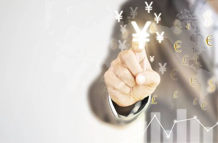 Businessman finger touch to YEN sign among Pound sterling US dollar and  EURO sign currency. YEN  is main and popular currency of exchange in the world.Investment and saving concept. Imagens