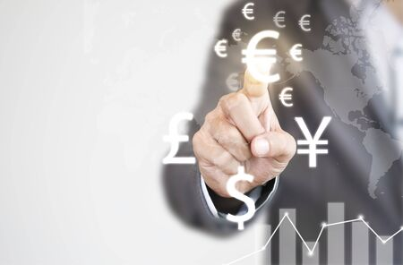 Businessman finger touch to euro sign among YEN dollar and Pound sterling sign currency. EURO  is main and popular currency of exchange in the world. Investment and saving concept.
