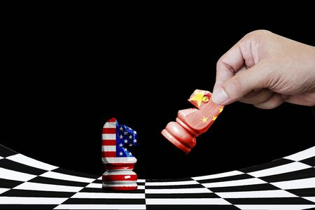 USA and China flag print screen on horse chess with black background. It is symbol of economic tariffs trade tax barrier between United States of America and China. Фото со стока