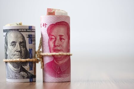 US dollar and Yuan banknote on wooden table. Its is symbol for tariff trade crisis between United States of America and China which the biggest economic country in the world. Stock Photo