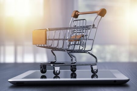 Closeup of shopping cart on parking on tablet. Online shopping and work from home concept.