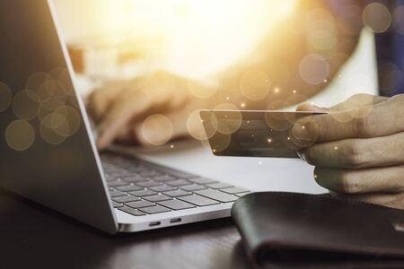 One hand holding credit card and another hand input order to computer laptop with shopping cart background. Online shopping and work from home concept.