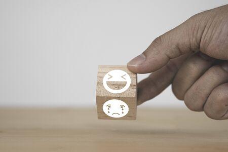 Main du client renversant l'émotion du visage heureux et souriant qui imprime un écran sur un bloc de bois sur un visage d'émotion triste. Évaluation du service client et concept d'espace de copie.