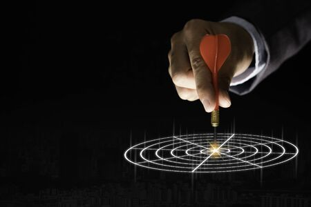 Businessman hand holding and trowing red dart to target board on black background.Business and investment target concept.