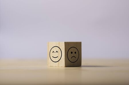 Two opposite side of emotion of happy and sad which print screen on wooden cubic. Customer experience survey and satisfaction feedback concept. Stok Fotoğraf