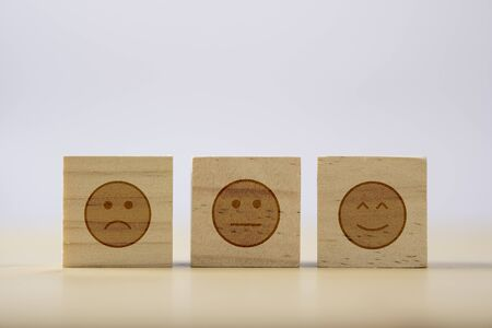 smiley emotion to among normal and sad emotion which print screen on wooden cubic. Customer experience survey and satisfaction feedback concept. Stok Fotoğraf