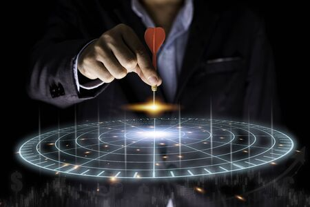 Businessman throwing red arrow dart to virtual target dart board. Setup objectives and target for business investment concept. Stock Photo