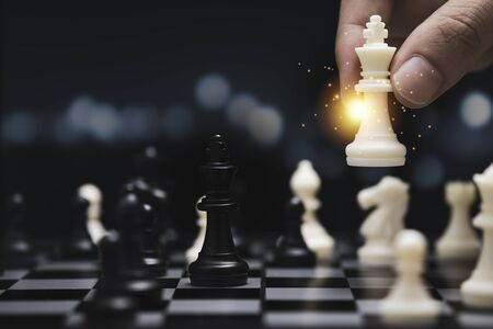 Businessman hand holding and moving white king chess figure with competitor to success play. Business management   competition and leadership concept.