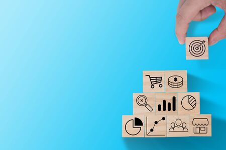 Hand putting target icon print screen on wooden cube to stack on other investment icon such as graph , dollar coin and trolley cart. Business investment concept. Zdjęcie Seryjne