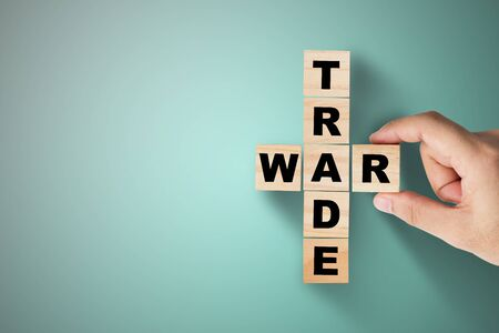 Hand putting trade war wording on green background.