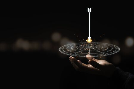 Hand holding virtual target board and arrow with bokeh background. Keeping and setup objectives and target for business investment concept.