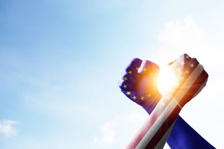USA flag and EU flag print screen fists and wrestling with blue sky and sunlight. United States of America and European Union have conflicted and barrier tariffs trade war. Zdjęcie Seryjne