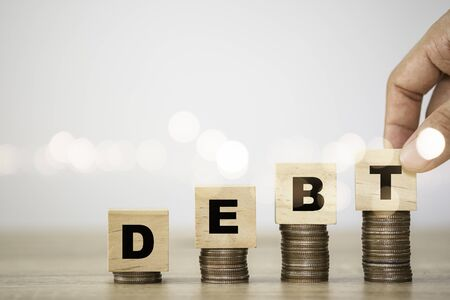 Hand putting debt wording which are printed screen to wooden cubes on coins stacking. Debt increasing concept.
