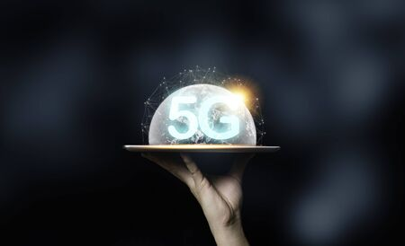 Hand holding tablet with 5G wording and virtual world illustration. Technology transformation concept. Zdjęcie Seryjne