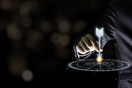 Businessman hand holding and throwing virtual dart to target board on black background.Business and investment target concept.