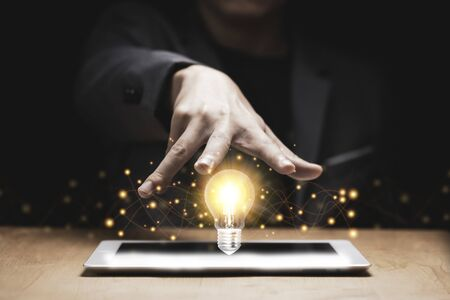 Businessman hand cover on lightbulb glowing with orange light on tablet. Creating and idea concept. Zdjęcie Seryjne
