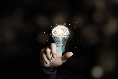 Hand touching the virtual light bulb with brain. Creative new business idea concept. Zdjęcie Seryjne - 147641735