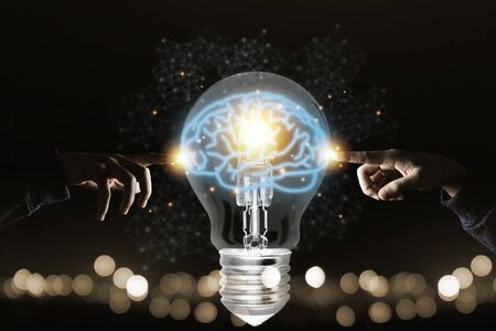 Two hands touching the virtual light bulb with brain. Creative new business idea concept.