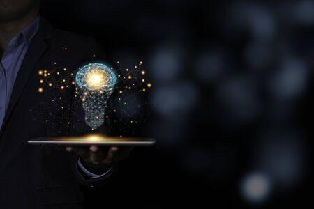 The virtual light bulb with brain on tablet. Creative new business idea concept. Zdjęcie Seryjne - 147641737