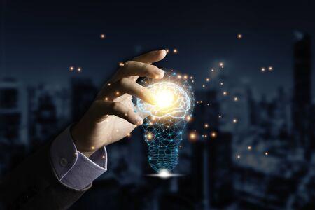 Hand holding the virtual light bulb with brain. Creative new business idea concept.
