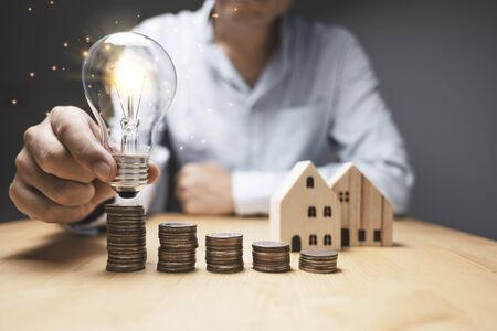 Businessman holding and putting light bulb to coins stacking. Creative new business idea can make profit money concept.