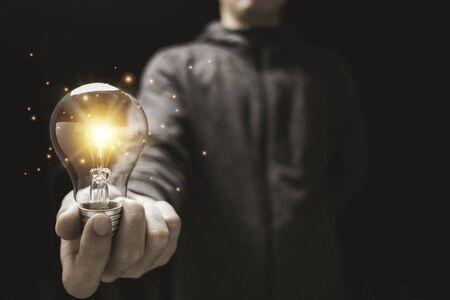 Businessman holding glowing lightbulb with orange light . Creative new business idea concept. Zdjęcie Seryjne