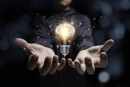 Businessman holding glowing lightbulb with virtual brain and orange light . Creative new business idea concept.